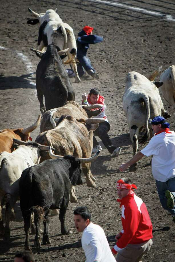 Hugo Soto, 21, of Pasedena, center, braces for impact with a bull after getting tangled up in the center of the lane during the Great Bull Run at Royal Purple Raceway, Saturday, Jan. 25, 2014, in Baytown.  Soto, was taken to an area hospital by ambulance. Photo: Michael Paulsen, Houston Chronicle / © 2014 Houston Chronicle