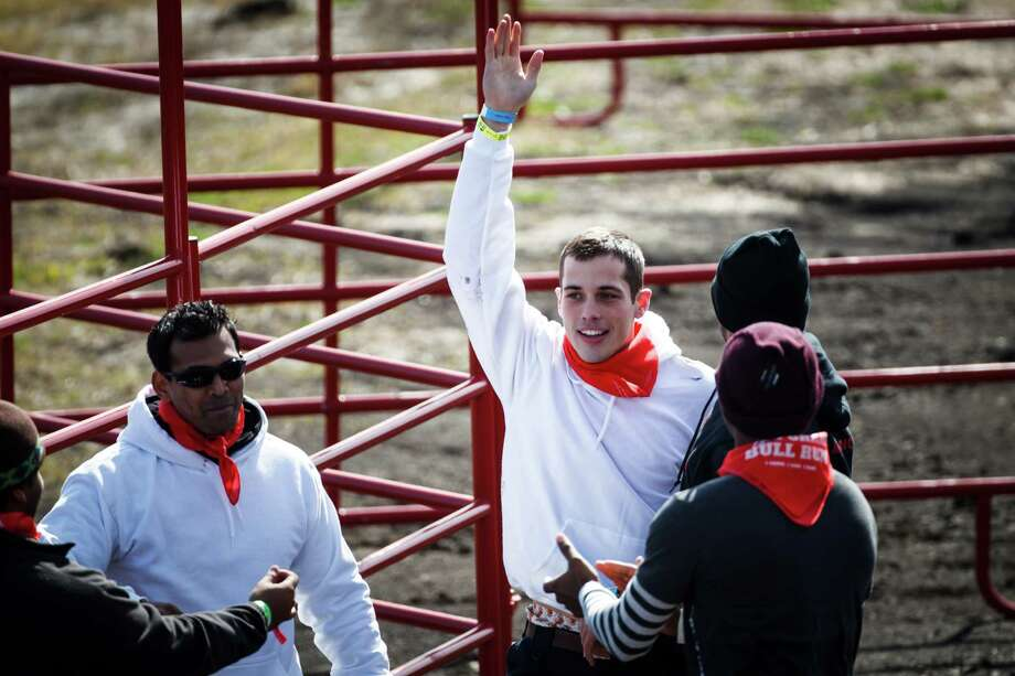 Chris Robertson waves to the crowd after being run over by a bull as he and other adventure seekers take part in the Great Bull Run at Royal Purple Raceway, Saturday, Jan. 25, 2014, in Baytown. Photo: Michael Paulsen, Houston Chronicle / © 2014 Houston Chronicle