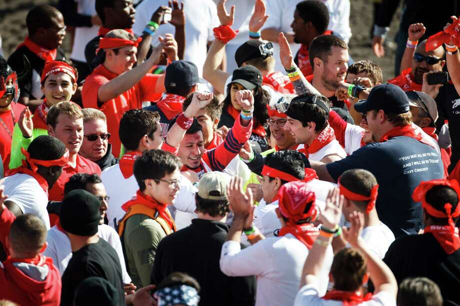Hugo Soto, 21, of Pasedena, center, is cheered by fans after getting trampled by several bulls during the Great Bull Run at Royal Purple Raceway, Saturday, Jan. 25, 2014, in Baytown.  Soto, was taken to an area hospital by ambulance. Photo: Michael Paulsen, Houston Chronicle / © 2014 Houston Chronicle