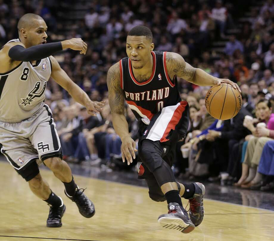 Damian Lillard drives around San Antonio's Patty Mills in a Jan. 17 win for Portland. Photo: Eric Gay, Associated Press