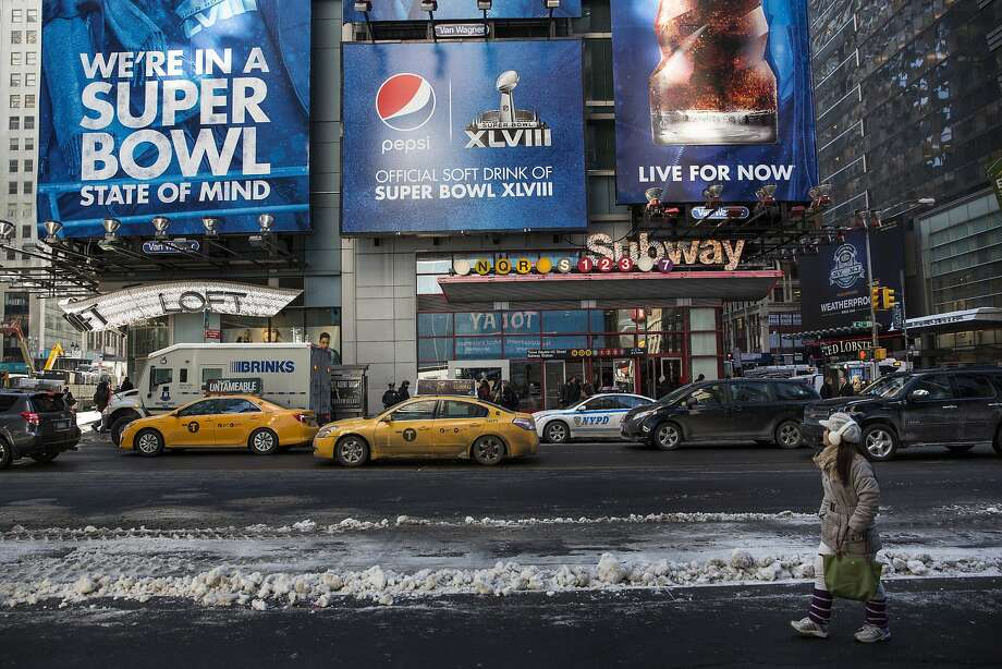 "New York City has turned sections of Times Square and Broadway into ""Super Bowl Boulevard"" as the championship game gets played in cold weather for the first time. Photo: Andrew Burton, Getty Images"