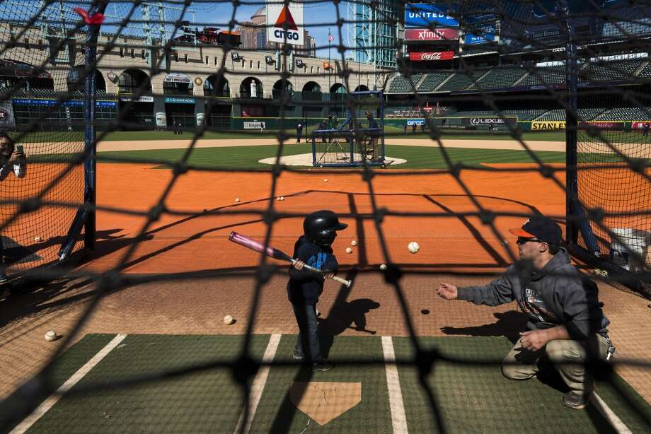 Isaac Estrada, 4, takes a swing at home plate as fans take batting practice during the Houston Astros Fanfest. Photo: Smiley N. Pool, Houston Chronicle