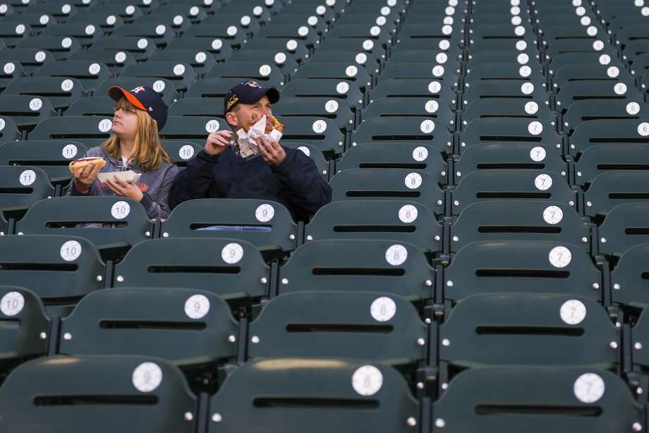Matt and Darcy Gresham look out over the stadium as they eat hot dogs and pretzels during the Houston Astros Fanfest. Photo: Smiley N. Pool, Houston Chronicle