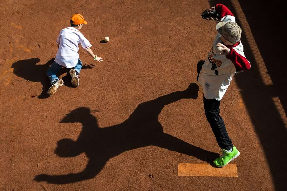 A young fans throw from the mound in the Houston Astros bullpen during the Houston Astros Fanfest. Photo: Smiley N. Pool, Houston Chronicle