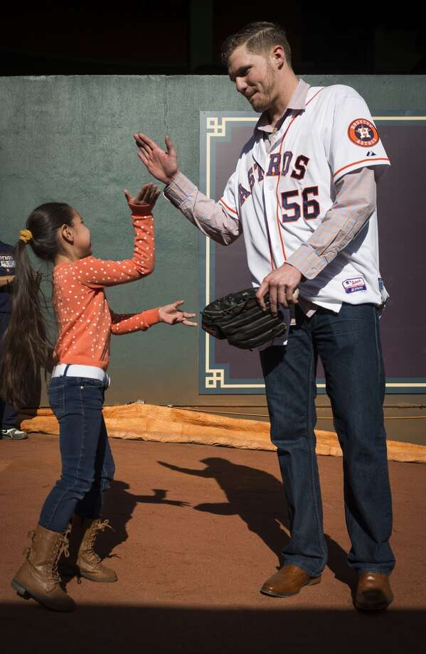 Celeste Diaz, 6, gets a high five from relief pitcher Paul Clemens after taking a turn pitching in Astros bullpen Photo: Smiley N. Pool, Houston Chronicle