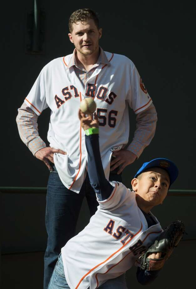 Tyler Morris, 9, throws a pitch in the Astros bullpen under the watchful eye of relief pitcher Paul Clemens during the Houston Astros Fanfest. Photo: Smiley N. Pool, Houston Chronicle