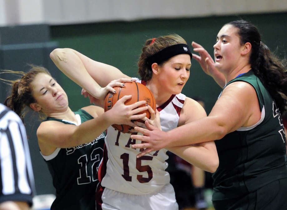 At left, Lilly O'Sullivan of Convent of the Sacred Heart (#12) and her sister and teammate, Emily O'Sullivan, right, attempt to take the ball away from Taft's Rylie Mainville (#15), during the girls high school basketball game between Convent of the Sacred Heart and Taft at the Convent in Greenwich, Saturday, Jan. 25, 2014. Taft defeated Convent of the Sacred Heart, 55-33. Photo: Bob Luckey / Greenwich Time