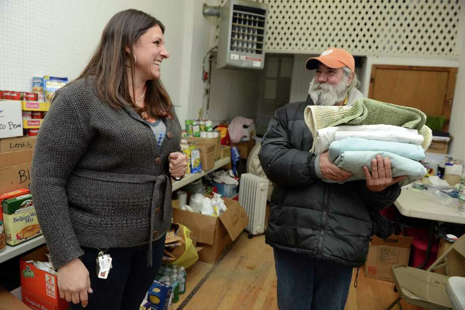 Volunteer Missy Samaha, of Stratford, helps Stephen Serrato gather supplies for his new apartment Saturday, Jan. 25, 2014, at a storefront on Center Street, owned by firefighter Chris Jones, being used to store donated food and supplies for victims of the fire on Howe Avenue in Shelton that destroyed businesses and apartments on January 6, 2014.  Echo Hose Hook & Ladder Co. was inundated with donations following the massive fire, but victims are still in need of housewares and kitchen supplies as they try to rebound. Photo: Autumn Driscoll / Connecticut Post