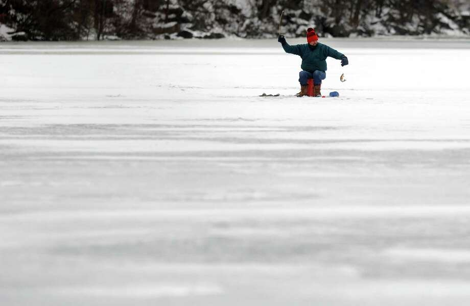 A fisherman holds up his catch while ice fishing Saturday, Jan. 25, 2014, at Pink House Cove on the Housatonic River in Derby, Conn. Photo: Autumn Driscoll / Connecticut Post