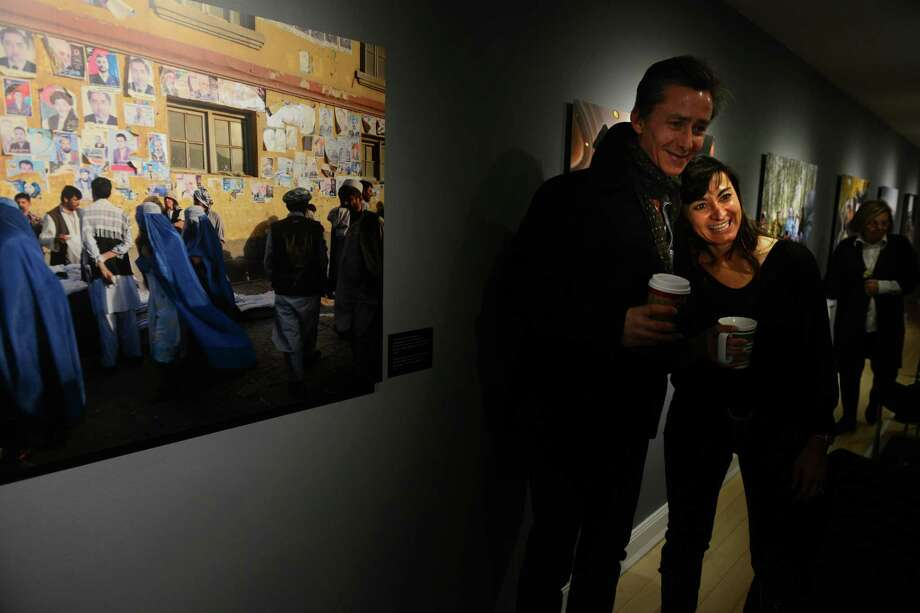 """Pulitzer Prize winning photojournalist Lynsey Addario, a Westport native, greets fellow photographer Spencer Platt as she exhibits """"On the Wire: Veiled Rebellion,"""" a photo essay that depicts the plight of women in Taliban-controlled Afghanistan, Saturday, Jan. 25, 2014, at the Westport Arts Center. Photo: Autumn Driscoll / Connecticut Post"""