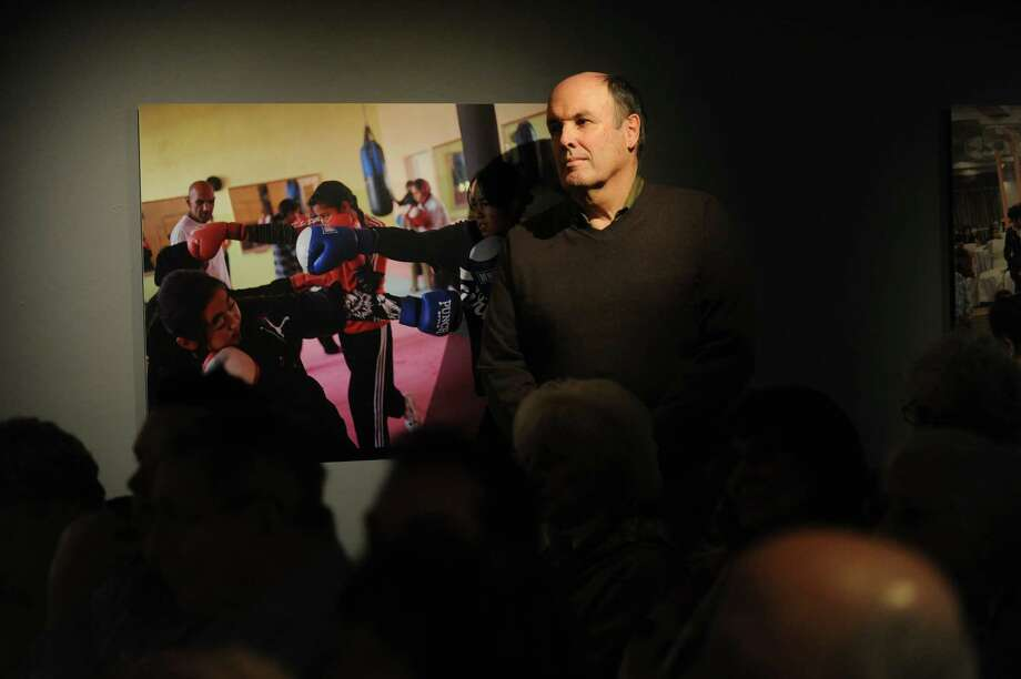 """Paul Davis stands beside a photograph from the exhibit """"On the Wire: Veiled Rebellion"""" by Pulitzer Prize winning photojournalist Lynsey Addario, a Westport native, at the Westport Arts Center Saturday, Jan. 25, 2014, as Addario speaks about her work. Photo: Autumn Driscoll / Connecticut Post"""