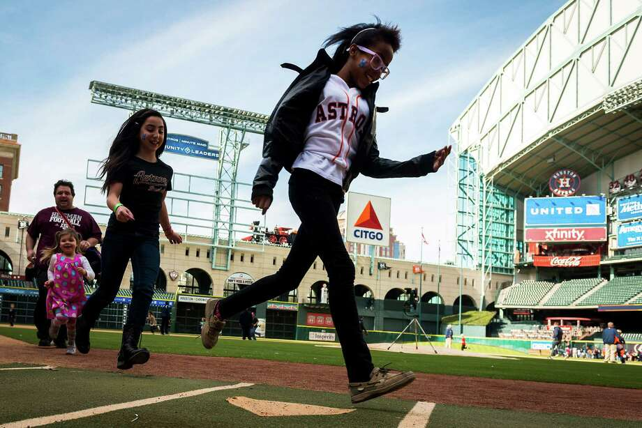Fans run the bases during Astros FanFest on Saturday at Minute Maid Park, where events included batting practice, photos in the dugout and story time with Milo Hamilton. Photo: Smiley N. Pool / © 2014  Smiley N. Pool