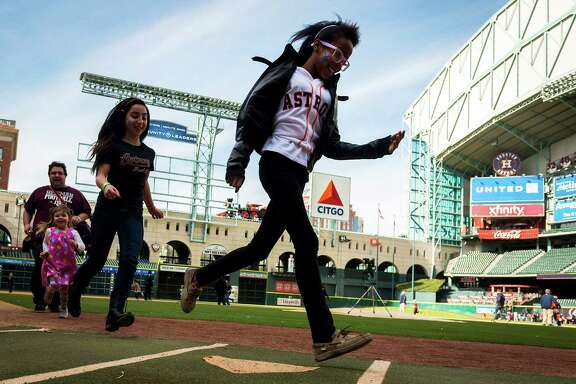 Fans run the bases during Astros FanFest on Saturday at Minute Maid Park, where events included batting practice, photos in the dugout and story time with Milo Hamilton.