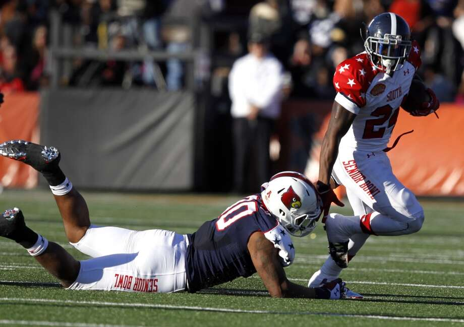 South running back Jerick McKinnon, of Georgia Southern, tries to get past the would be tackle of the North's Marcus Smith, of Louisville, during the first half. Photo: Butch Dill, Associated Press