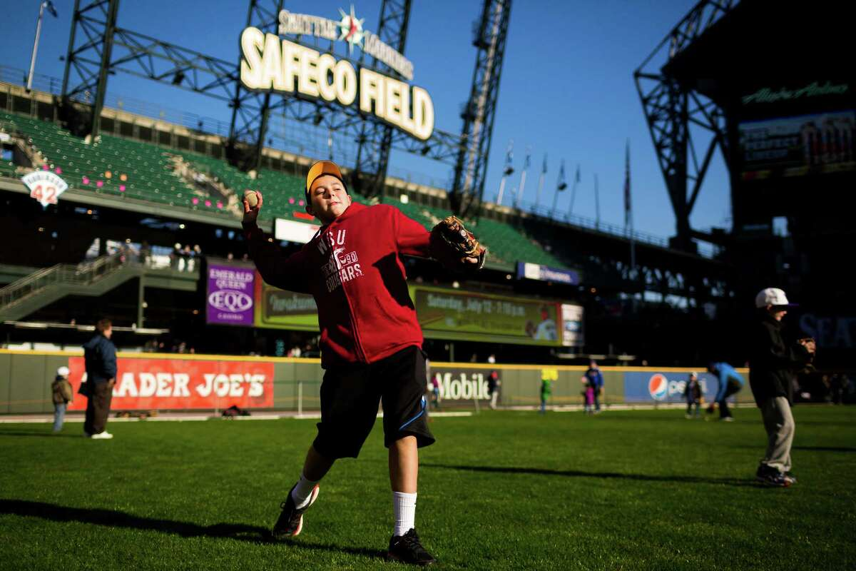 Brayden Castro, 12, center left, plays catch with his father, not pictured, during the 16th annual Mariners FanFest Saturday, Jan. 25, 2014, at Safeco Field in Seattle. Fans could tour the Mariners' clubhouse, ride two different zip lines over Safeco Field and hit a simulated Felix Hernandez fastball in a batting cage. The event runs from 11 a.m. to 4 p.m. on Sunday. Tickets are $10 for adults, with children 14 and under admitted for free.