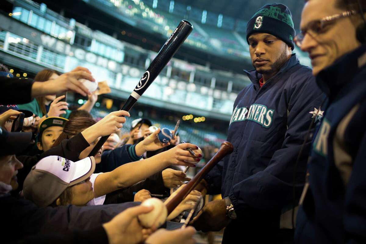 New Mariners second baseman Robinson Cano, center right, signs autographs for a horde of fans during the 16th annual Mariners FanFest Saturday, Jan. 25, 2014, at Safeco Field in Seattle. Fans could tour the Mariners' clubhouse, ride two different zip lines over Safeco Field and hit a simulated Felix Hernandez fastball in a batting cage. The event runs from 11 a.m. to 4 p.m. on Sunday. Tickets are $10 for adults, with children 14 and under admitted for free.