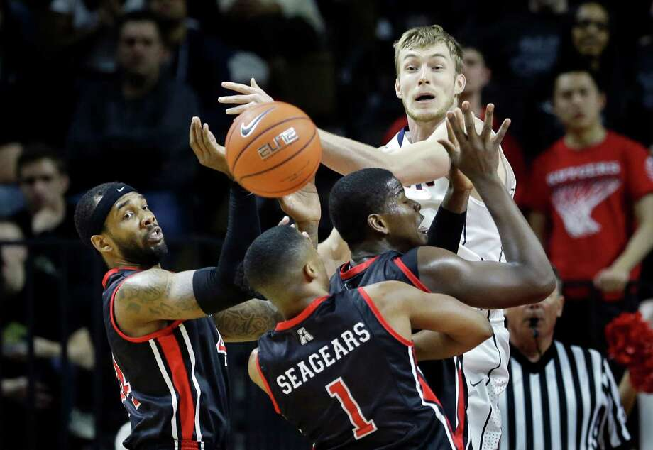Connecticut guard Niels Giffey, back, of Germany, can't hold onto the ball as he is swarmed by Rutgers defenders during the second half of an NCAA college basketball game Saturday, Jan. 25, 2014, in Piscataway, N.J. (AP Photo/Mel Evans) Photo: Mel Evans, Associated Press / Associated Press