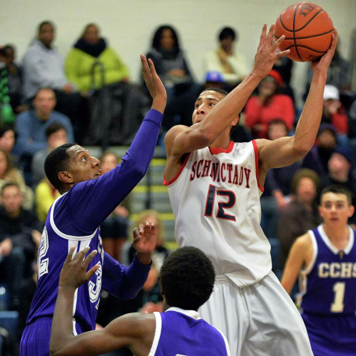 Schenectady's #12 Randall Symes, center, is guarded by CCHS's #32 Malik Miller during Saturday's game Jan. 25, 2014, in Schenectady, NY. (John Carl D'Annibale / Times Union)