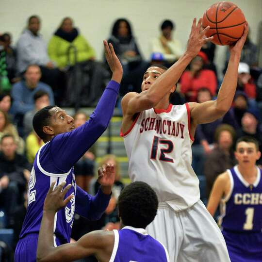 Schenectady's #12 Randall Symes, center, is guarded by CCHS's #32 Malik Miller during Saturday's gam