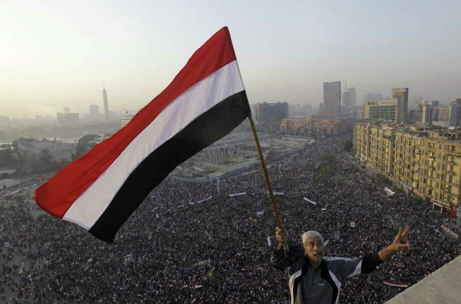 An Egyptian, eyes skyward, waves a national flag for military helicopters flying over a pro-military rally marking the third anniversary of the 2011 uprising in Tahrir Square in Cairo. Photo: Amr Nabil / Associated Press / AP