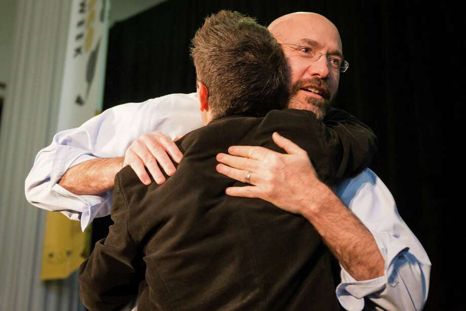 KIPP Co-Founder Mike Feinberg, facing, hugs Cristo Rey Jesuit College Preparatory School of Houston Founder and President Father T.J. Martinez during the Official Kickoff of National School Choice Week. ( Smiley N. Pool / Houston Chronicle ) Photo: Smiley N. Pool, Houston Chronicle / © 2014  Smiley N. Pool