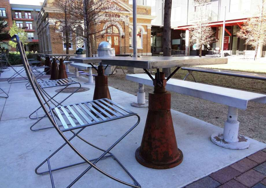Iron ballards that once supported large tanks have been converted to table bases outside Local Coffee. Photo: Photo By Steve Bennett