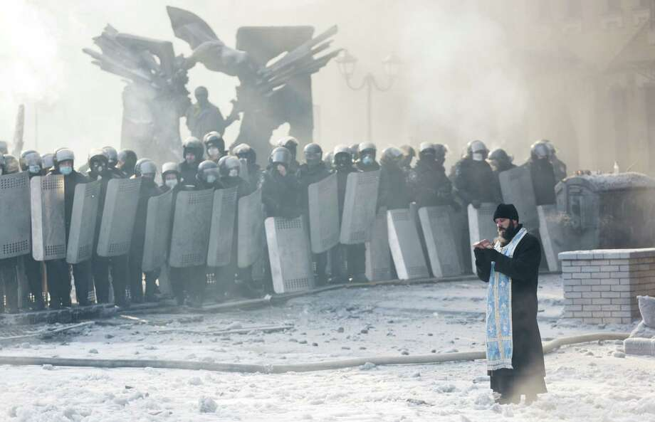 An Orthodox priest prays between police and protesters in Kiev, where opposition leaders rejected President Viktor Yanukovych's power-sharing offer. Photo: Rob Stothard / Getty Images / 2014 Getty Images
