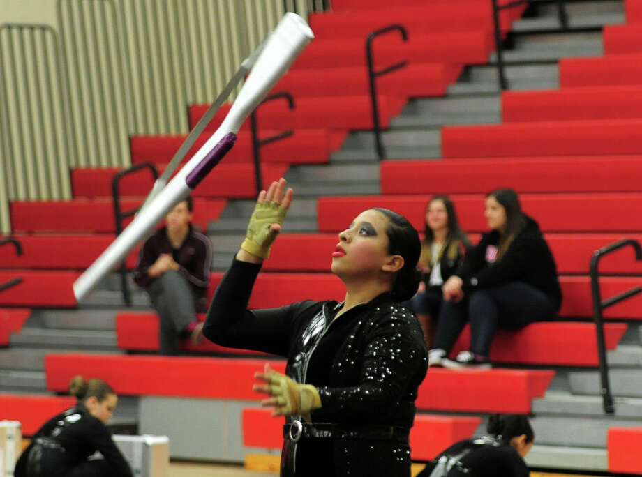 Norwalk Winterguard Team's Lesley Cordero-Santiago catches her rifle, during the Winterguard competition at Masuk High School in Monroe, Conn. on Saturday January 25, 2014. The Masuk Cologuard Team as well as the other teams who've assembled, are comprised of dedicated, passionate students who practice several hours each week. They perfect their skills of tossing and spinning flags, rifles, and sabres and aquire a combination of athletic skills, creative interpretation of music, and theatrical performance. Photo: Christian Abraham / Connecticut Post