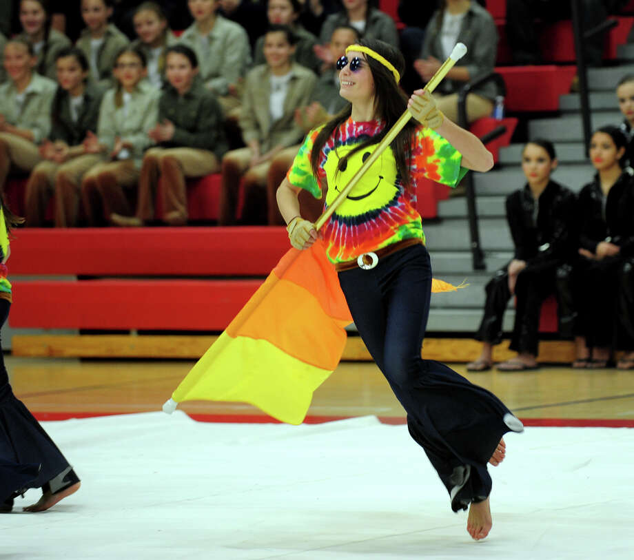 Moira McKinley, with the Newtown Junior Guard performs, during the Winterguard Competition at Masuk High School in Monroe, Conn. on Saturday January 25, 2014. The Masuk Cologuard Team as well as the other teams who've assembled, are comprised of dedicated, passionate students who practice several hours each week. They perfect their skills of tossing and spinning flags, rifles, and sabres and aquire a combination of athletic skills, creative interpretation of music, and theatrical performance. Photo: Christian Abraham / Connecticut Post