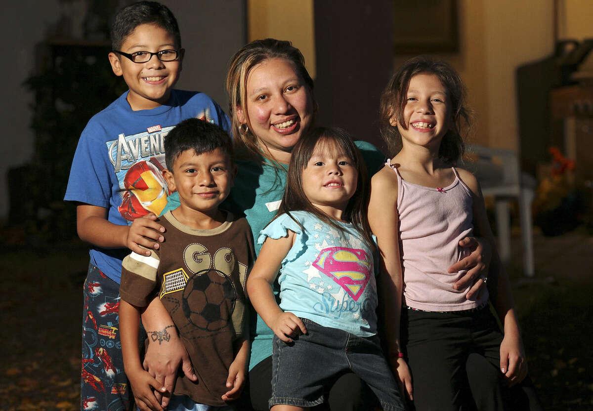 Portrait of Irma Aguilar (center) and her children Jacob Martinez, 10, (from left), Izaiah Aguilar, 5, Rihanna Aguilar, 4, and Monique Aguilar, 8, Thursday Nov. 21, 2013 at their home.