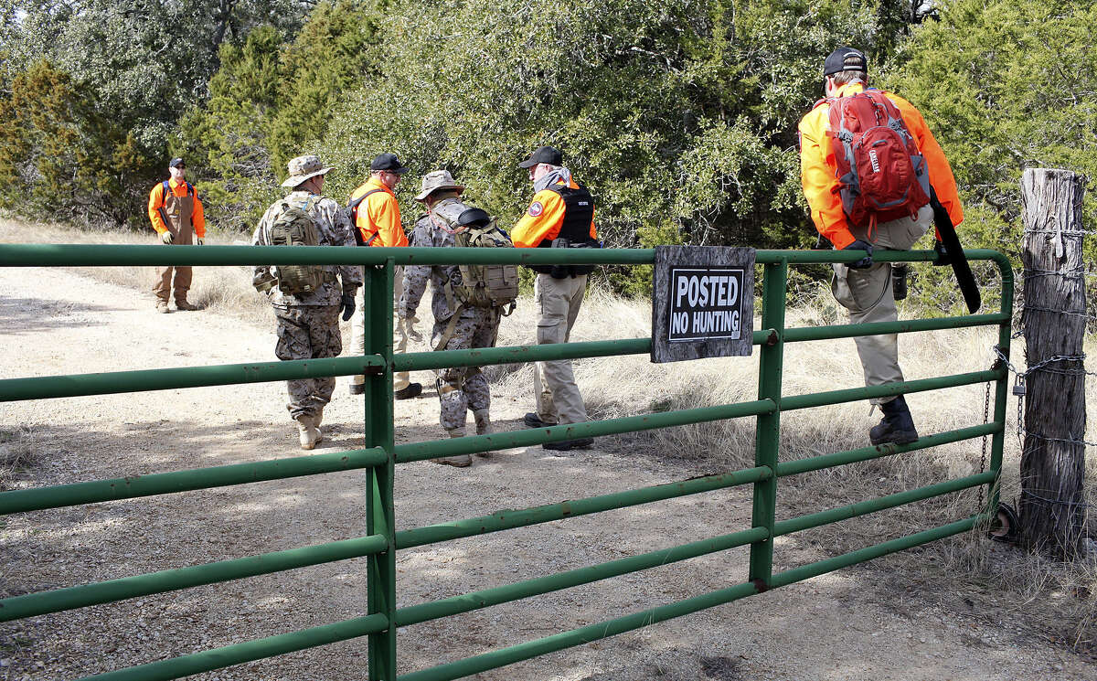 Searchers climb over a gate to look for Leanne Hecht Bearden off of Schoenthal Road.