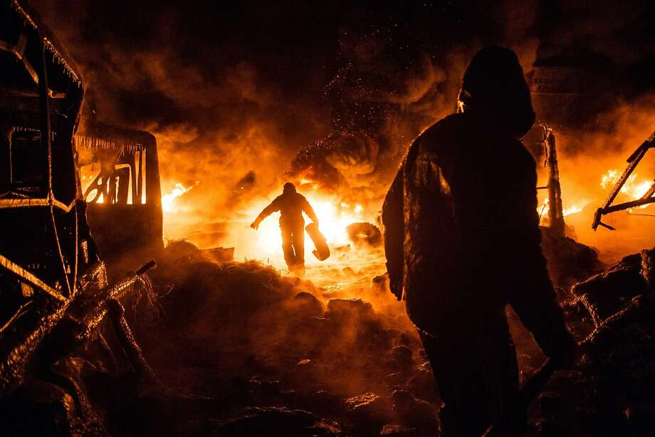 TOPSHOTS Ukrainian anti-government protesters walk past burning tyres during clashes with riot police in central Kiev early on January 25, 2014. Protesters and Ukrainian police were locked in a tense standoff in Kiev after a night of sporadic clashes that erupted despite a truce and offer of concessions by President Viktor Yanukovych. AFP PHOTO / VOLODYMYR SHUVAYEVVOLODYMYR SHUVAYEV/AFP/Getty Images Photo: Volodymyr Shuvayev, AFP/Getty Images