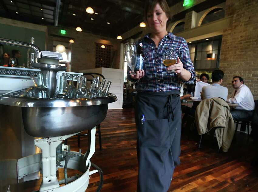 Elizabeth Speer, a server at Cured, passes a salvaged hand-cleaning station that now serves as a water bottle chiller at the restaurant.