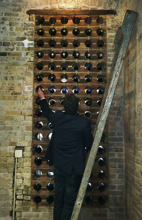 Dee Coram stocks wine bottles at Cured in a holder made from contoured bricks taken from the old Pearl brewery. Shops at the Pearl are encouraged to reuse items left over from the old brewery. Photo: Bob Owen / San Antonio Express-News / © 2012 San Antonio Express-News
