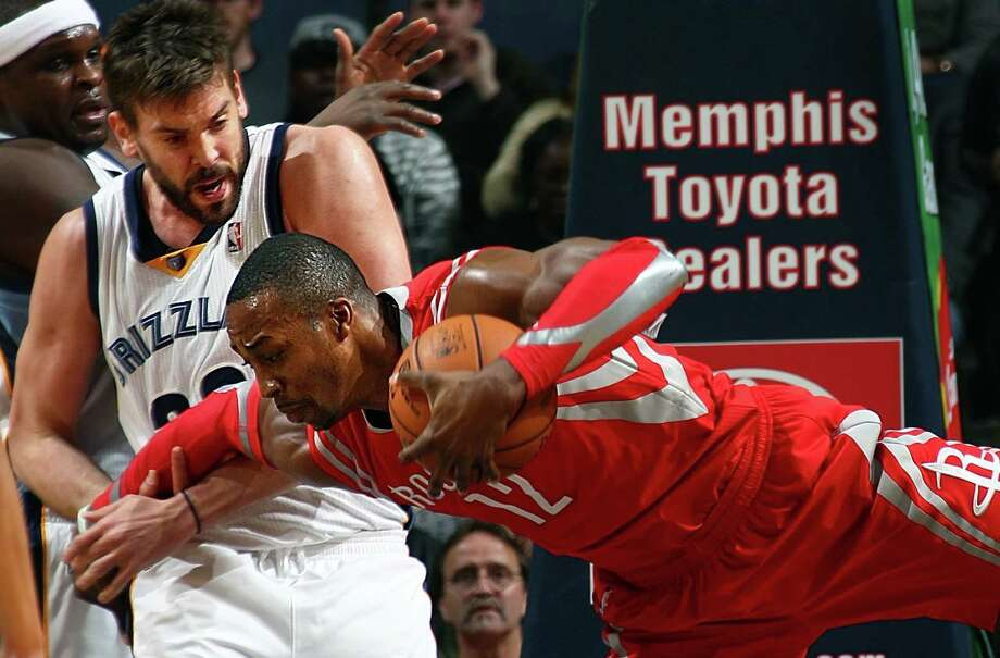 Grizzlies center Marc Gasol (center), who was limited to six points and five rebounds, fouls Rockets center Dwight Howard. Memphis won the game 99-81 as Howard had 10 points and 12 rebounds. Photo: Nikki Boertman / The Commercial Appeal / The Commercial Appeal