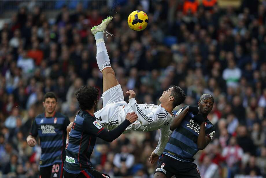 Real Madrid's Cristiano Ronaldo from Portugal, top, tries to score in between opposition players during a Spanish La Liga soccer match between Real Madrid and Granada at the Santiago Bernabeu stadium in Madrid, Spain, Saturday, Jan. 25, 2014. (AP Photo/Andres Kudacki) Photo: Andres Kudacki, Associated Press