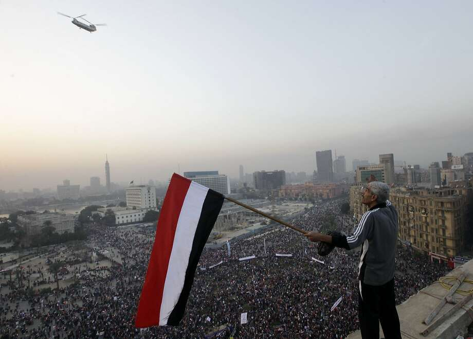 An Egyptian waves a national flag for a military helicopter flying over a pro-military rally marking the third anniversary of the 2011 uprising in Tahrir Square in Cairo, Egypt, Saturday, Jan. 25, 2014. Egyptian riot police have fired tear gas to disperse hundreds of supporters of ousted Islamist President Mohammed Morsi protesting as the country marks the third anniversary of the 2011 uprising, as supporters of the military gathered in rival rallies in other parts of the capital, many of them urging military chief Gen. Abdel-Fattah el-Sissi, the man who removed Morsi, to run for president. (AP Photo/Amr Nabil) Photo: Amr Nabil, Associated Press