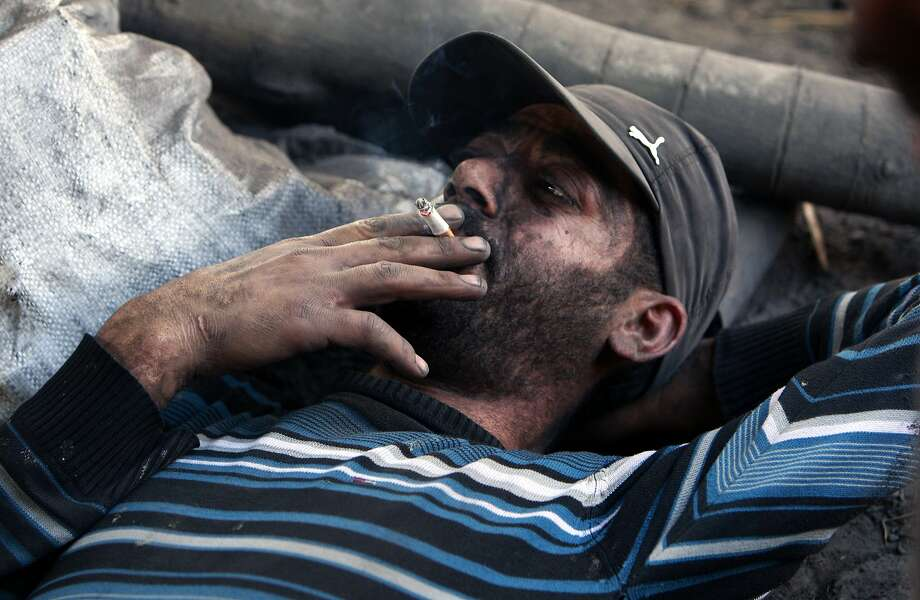 A Palestinian worker takes a rest from collecting charcoal in the West Bank village of Yabed, near Jenin city, Saturday, Jan. 25, 2014. More than a thousand Palestinian families in the village depend on charcoal production as their main source of income. The charcoal is later sold to Israelis and Palestinians for approximately 8 shekels, more than 2 U.S. dollars per kilogram.(AP Photo/Mohammed Ballas) Photo: Mohammed Ballas, Associated Press