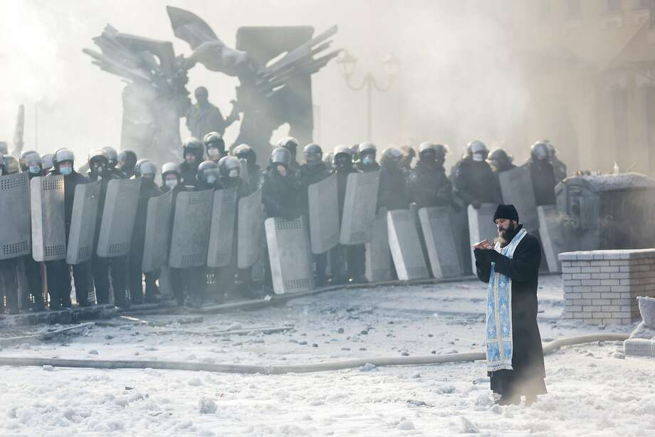 KIEV, UKRAINE - JANUARY 25: An Orthodox priest prays between police and protestors at the scene of anti-government protests near Dynamo Stadium on January 25, 2014 in Kiev, Ukraine. Violent protests in Ukraine have spread beyond the capital as President Viktor Yanukovych held crisis talks with three key opposition leaders. (Photo by Rob Stothard/Getty Images) *** BESTPIX *** Photo: Rob Stothard, Getty Images