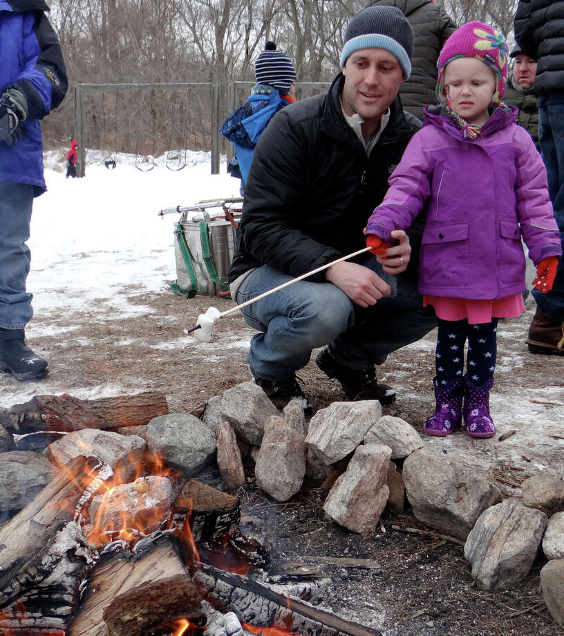 Erik Walsh and daughter Emma, 3, of Westport, toast marshmallows Saturday at the Winterfest celebration at Earthplace. Photo: Mike Lauterborn / Westport News contributed