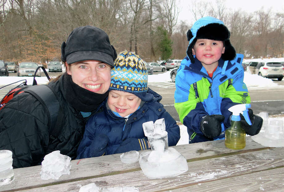 Amanda Elliott, of Westport, with son Tyler, and Aedan Messina, 4, of Southport, sculpt ice at Earthplace on Saturday. Photo: Mike Lauterborn / Westport News contributed