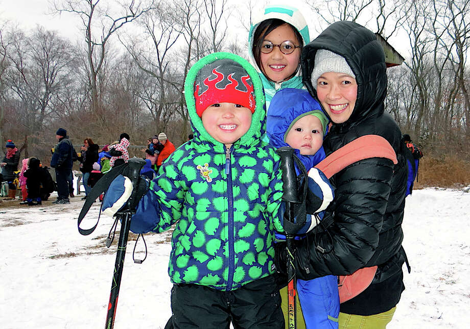 Laura Lewis, of Weston, and her children Ari, 4; Nima, 10, and Theodore, 1, try out snowshoes and other outdoor pursuits at Earthplace on Saturday. Photo: Mike Lauterborn / Westport News contributed
