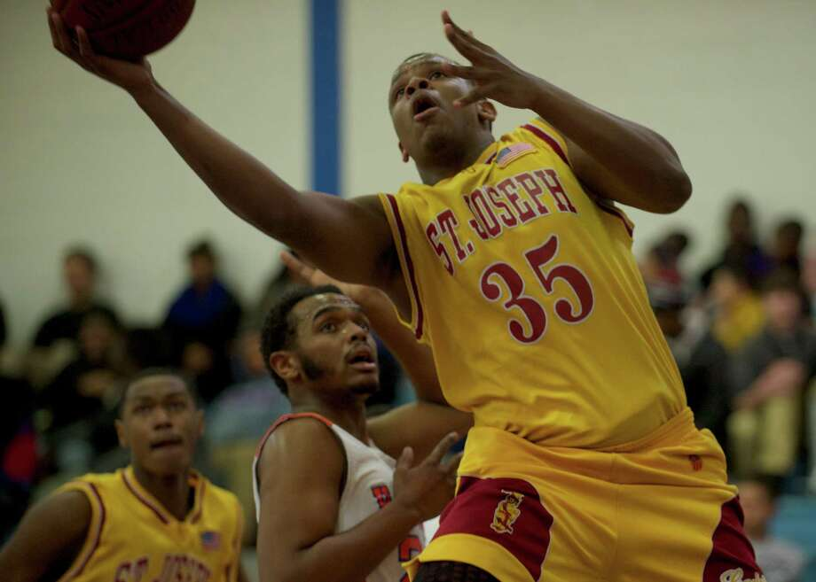 St Joseph's Erick Langston, 35, drives to the basket past Danbury's Jamar Peterson, 22, during a boys FCIAC basketball game, St Josephs, of Trumbull, at Danbury High School, Danbury, Conn on Thursday, January 23, 2014. Photo: H John Voorhees III / The News-Times Freelance