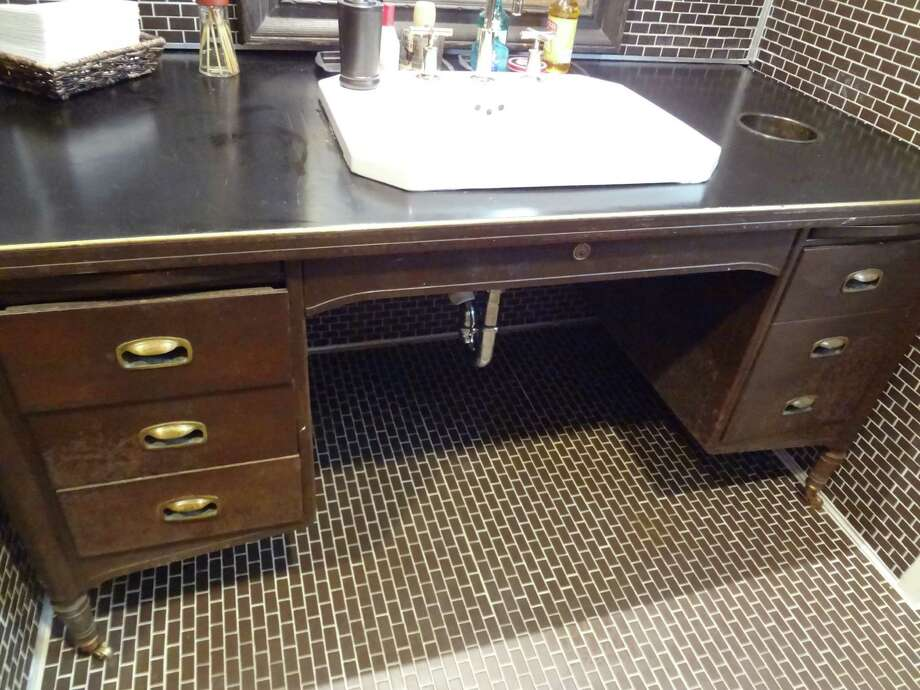 An old office desk found new meaning in life as a men's bathroom countertop. Photo: Photo By Steve Bennett