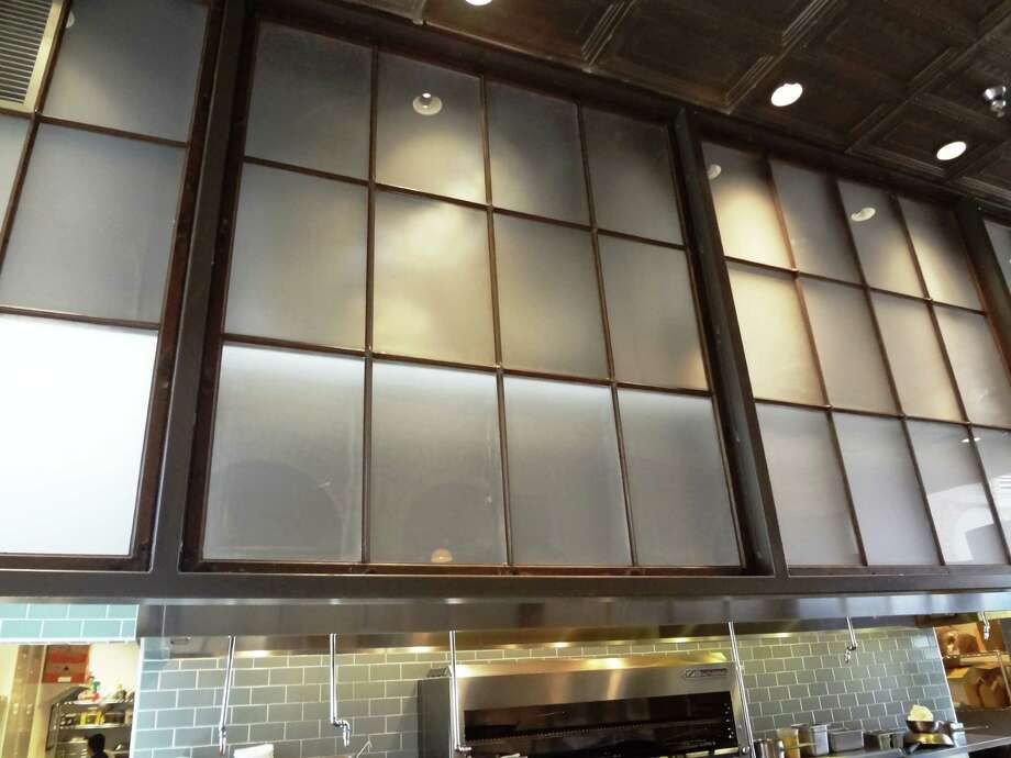 Old window grids were repurposed as protective partial walls in the kitchen. Photo: Photo By Steve Bennett