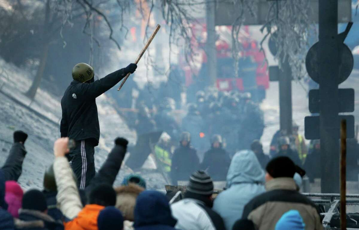 People stand behind the barricade in front of riot police in central Kiev, Ukraine, Sunday, Jan. 26, 2014. Ukraine's opposition called off a massive rally planned for Sunday because of the funeral for a protester killed in clashes with police last week, underscoring the rising tensions in the country's two-month political crisis. The opposition contends they were shot by police in an area where demonstrators had been throwing rocks and firebombs at riot police for several days.