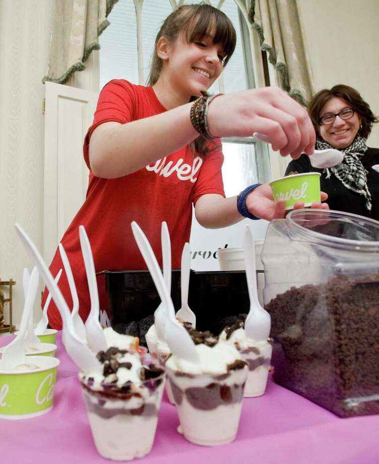 Carvel employee Aspen Shafer puts a topping on a Mini Dasher ice cream cup as manager Lori Soyak watches at the 15th annual Taste of Ridgefield held at the Ridgefield Community Center. Sunday, Jan. 26, 2014 Photo: Scott Mullin / The News-Times Freelance