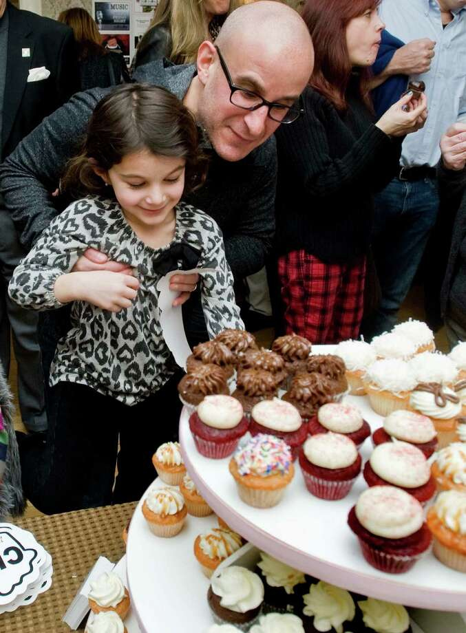 Matt Rutig of Ridgefield lifts his daughter Lily, 6, so she can select a mini cupcake from the Cake Box at the 15th annual Taste of Ridgefield held at the Ridgefield Community Center. Sunday, Jan. 26, 2014 Photo: Scott Mullin / The News-Times Freelance