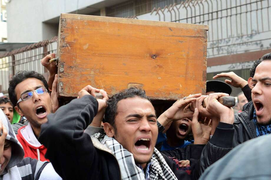 The coffin of one of the victims of clashes between supporters and opponents of Egypt's military is carried outside the Zinhom Morgue on January 26, 2014, outside Cairo, Egypt. Nearly 50 people died in weekend clashes between supporters and opponents of Egypt's military, as media outlets on January 25, 2014 hailed rallies urging the army chief to run for the presidency.    AFP PHOTO MOHAMED EL-SHAHEDMOHAMED EL-SHAHED/AFP/Getty Images Photo: Mohamed El-shahed, AFP/Getty Images