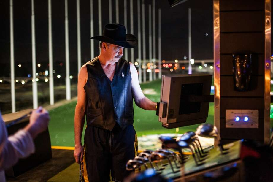 Thomas Chorba, a platinum member at Top Golf, checks the touch screen during the Suits and Boots party on Saturday, Jan. 25, in Houston. (Michael Starghill Jr. / For the Houston Chronicle) Photo: Michael Starghill Jr. / For The Houston Chronicle